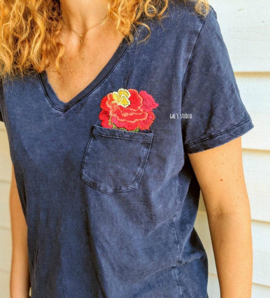 אישה עם חולצה כחולה ורקמת פרחים מבצבצת מהכיס