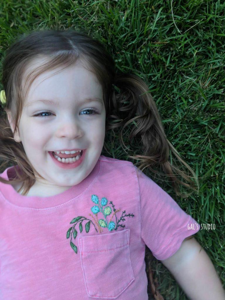 ילדה צוחקת בדשא עם חולצה רקומה בפרחים