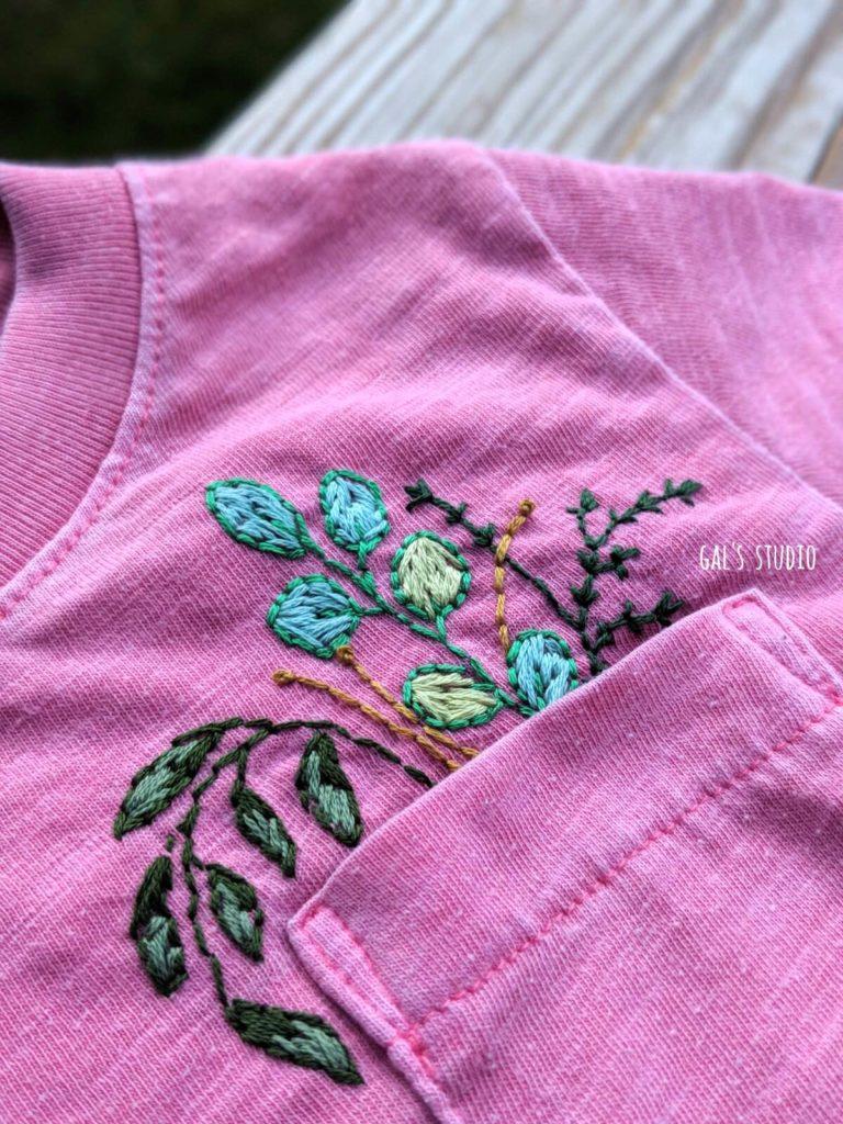 חולצה ורודה לילדה עם פרחים רקומים בכיס