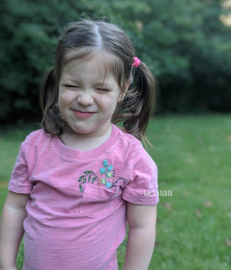 ילדה בחולצה רקומה עושה פרצוף מצחיק