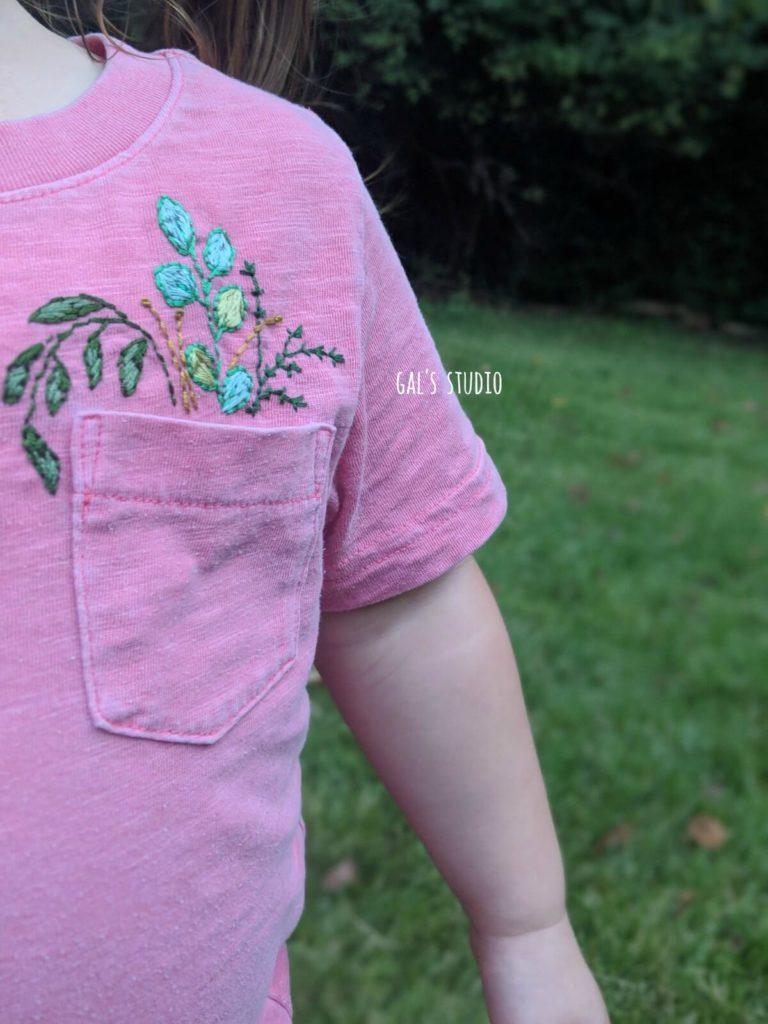 חולצה ורודה של ילדה עם רקמת פרחים בכיס