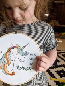 ילדה מחזיקה חישוק רקמה של חד קרן