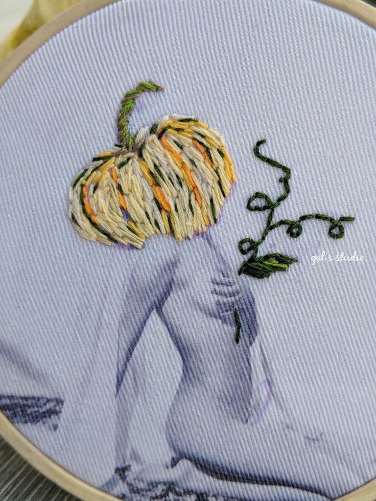 תקריב צילום אישה על בד עם ראש דלעת רקום