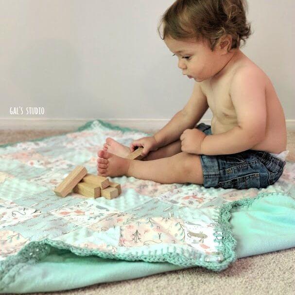 פעוט משחק בקוביות על שמיכה