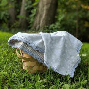 שמיכת תינוק על סלסלת קש ביער