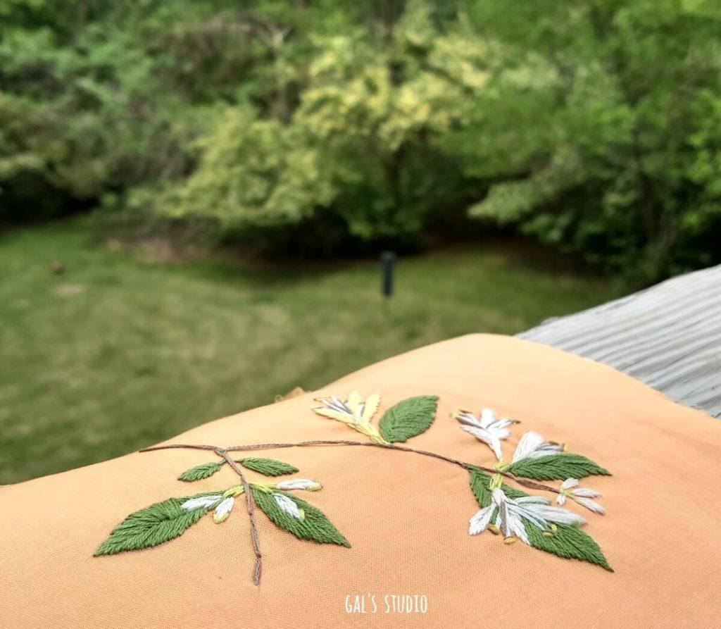 בד כתום פרוש על המעקה בגינה ועליו רקמת פרח
