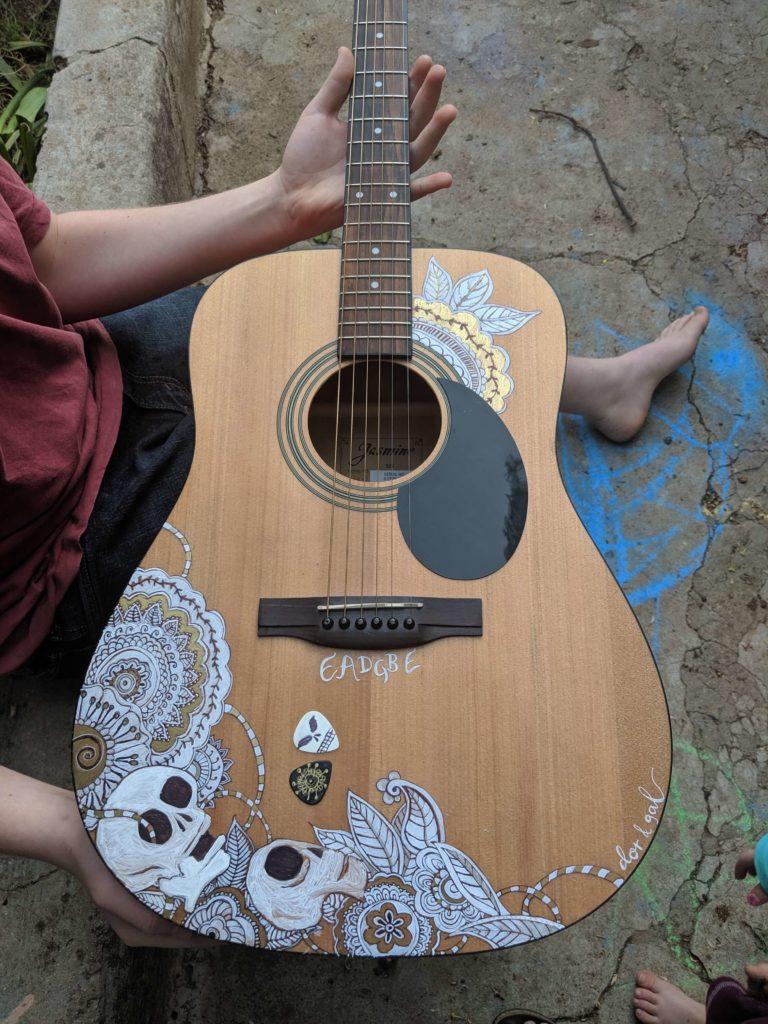 גיטרה עם ציורי גולגלות לבנות ועיטורים בשחור וזהב