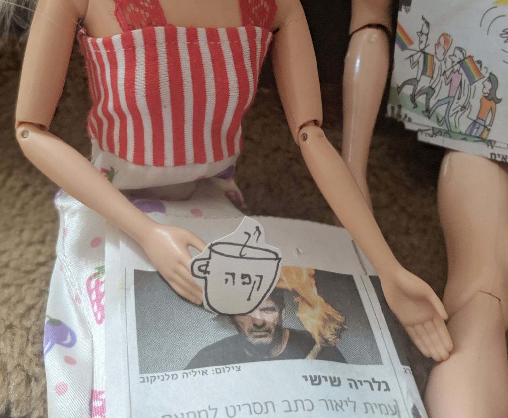 יד של ברבי אוחזת ספל קפה מקרטון על רקע עיתון לברביות