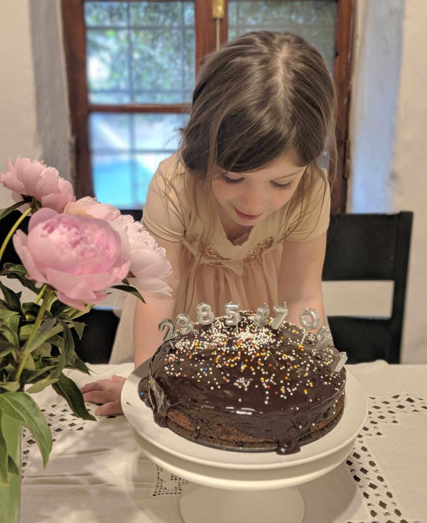 גוני במלה חגיגית וורודה ליד עוגת יומולדת עם מלא נרות