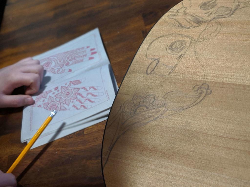 סקיצות על גבי גיטרה קלאסית וברקע חוברת קעקועי חינות הודית