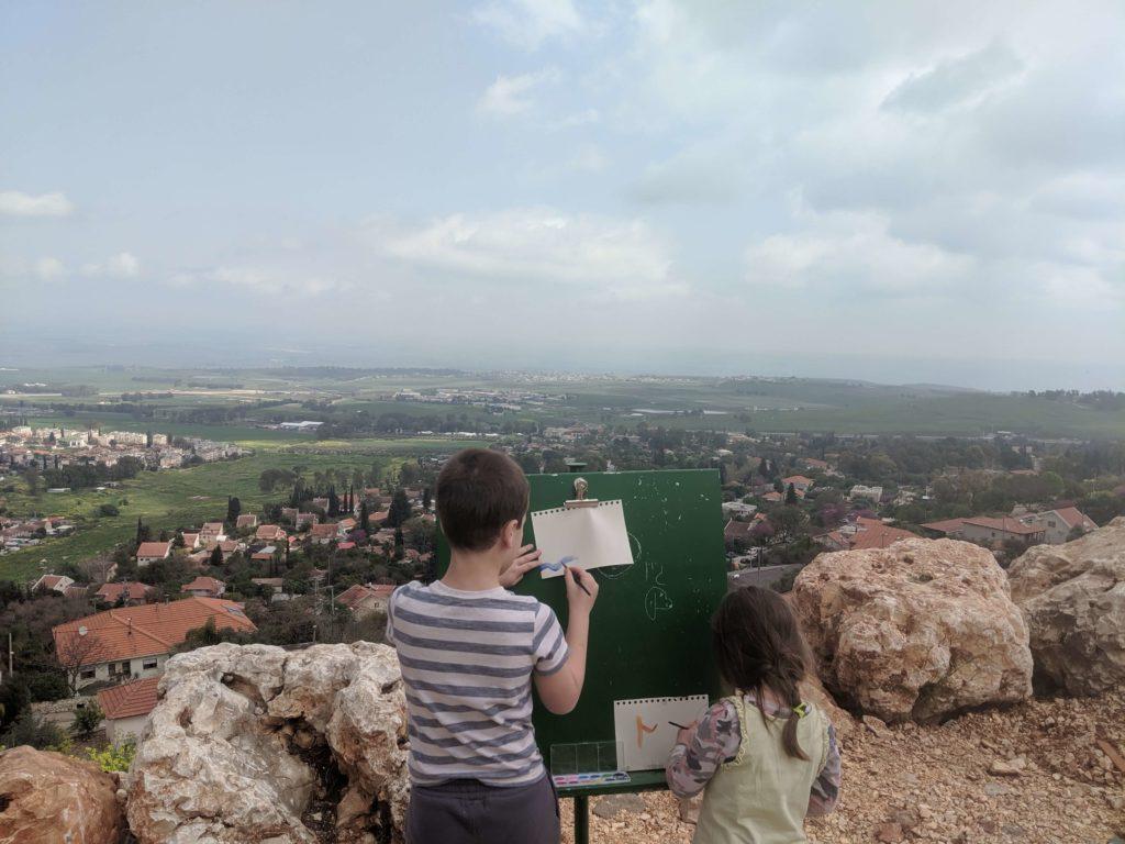 נטע וגוני מציירים בצבעי מים מול הנוף הנשקף מתצפית בראש פינה