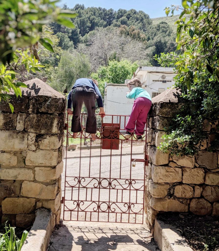 ילדים מטפסים על שער הכניסה לבית