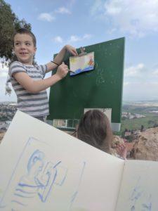 מחברת הסקיצות שלי עם שרבוט ילד וברקע נטע מצייר בצבעי מים