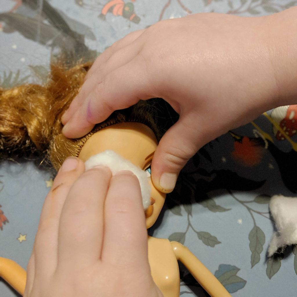 ידיים קטנות משפשפות עם צמר גפן את הפנים של הבובה